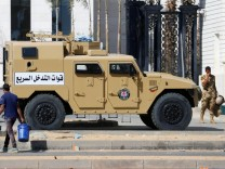 Egyptian Army soliders guard in front of Al Masah Capital Management Ltd. near Cairo