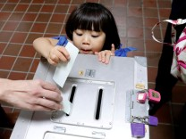 A girl casts her father's ballot for a national election at a polling station in Tokyo