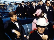 Texas Governor John Connally foreground adjusts his tie as President John F Kennedy and his wife