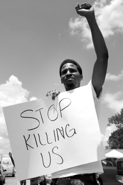 Lakeith Howard demonstrates outside the Triple S Food Mart where Alton Sterling was shot dead by police in Baton Rouge