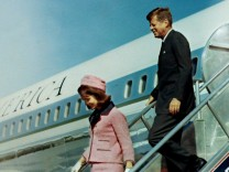 FILE PHOTO: U.S. President John F. Kennedy and first lady Jacqueline Bouvier Kennedy walk down the steps of Air Force One as they arrive at Love Field in Dallas
