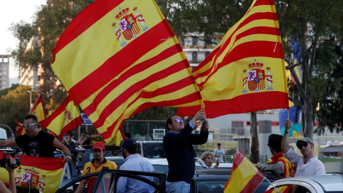 Pro-unity demonstrators wave the Spanish and Catalan flags as they gather in Barcelona
