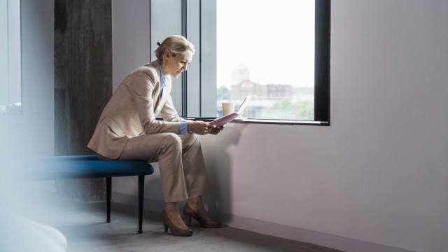 Businesswoman sitting at the window reading document model released Symbolfoto property released PUB