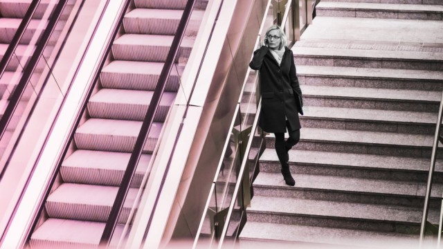 Businesswoman on stairs with cell phone model released Symbolfoto PUBLICATIONxINxGERxSUIxAUTxHUNxONL