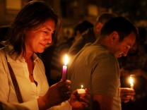 A woman weeps as she holds candles outside the Instituto Politecnico high school
