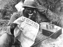 August 9 1950 U S soldier reads the latest news while enjoying chow during lull in battle agains
