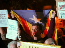 A man with his tapped mouth holds an Estelada (Catalan separtist flag) during a gathering in support of the members of the dismissed Catalan cabinet after a Spanish judge ordered the former Catalan leaders to be remanded in custody pending an inve