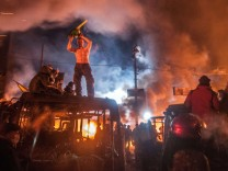 Jan 25 2014 Kiev Ukraine A protester on a burned bus holds a chainsaw as confrontations betwe