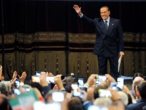 Forza Italia party leader Silvio Berlusconi waves to his supporters during a rally for the regional election in Palermo