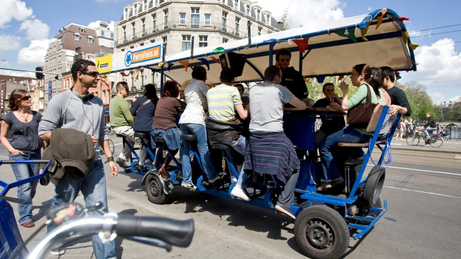 FILE PHOTO - Tourists cycle as they drink beer and sing karaoke on a beer bike in Amsterdam