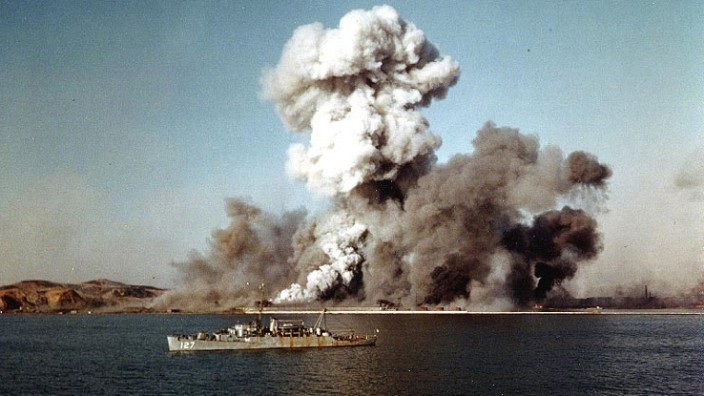 Smoke rises over Hungnam's port area, as facilties and remaining U.N. supplies are demolished by explosives on the final day of evacuation operations