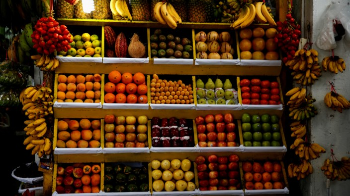 Bananas, apples, mangoes, strawberries, pineapples and other fruits are on display for sale at a market in Lima