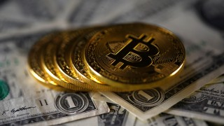 Bitcoin (virtual currency) coins placed on Dollar banknotes are seen in this illustration picture