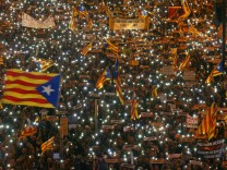 Protesters hold the lights of their mobile phones as they wave Estelada flags during a demonstration called by pro-independence associations asking for the release of jailed Catalan activists and leaders, in Barcelona