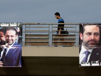 Posters depicting Lebanon's Prime Minister Saad al-Hariri, who has resigned from his post, are seen in Beirut