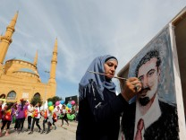 Youmn Ahmad, a Lebanese artist, paints a portrait of Lebanon's Prime Minister Saad al-Hariri, who has resigned from his post, during the annual Beirut Marathon
