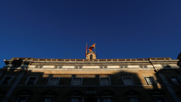 Spanish and Catalan flags flutter atop the Generalitat Palace, the Catalan regional government headquarters in Barcelona