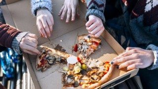 Four friends eating pizza outdoors partial view model released Symbolfoto PUBLICATIONxINxGERxSUIxAU