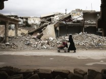 A woman pushes a baby trolley past damaged buildings in the rebel held besieged city of Douma