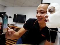 Ngo Tuan Anh, Vice President of Bkav, a Vietnamese cybersecurity firm, demonstrates iPhone X Apple's face recognition ID software with a 3D mask at his office in Hanoi