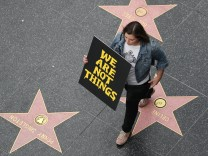 A demonstrator takes part in a #MeToo protest march for survivors of sexual assault and their supporters on the Hollywood Walk of Fame in Hollywood, Los Angeles