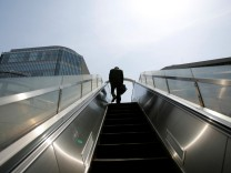 FILE PHOTO: A businessman rides on an escalator in Tokyo's business district