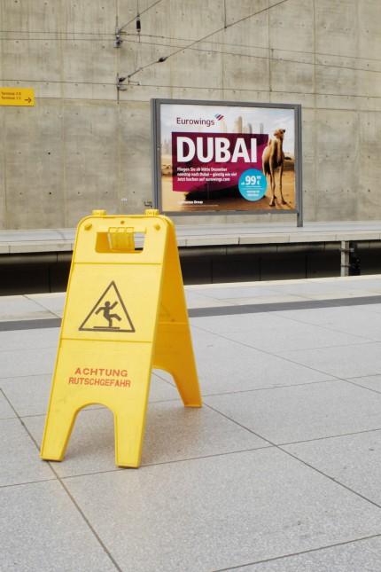 Köln Bonn Airport GER 05 11 2015 Aufsteller Vorsicht Rutschgefahr vor Werbeplakat für die Low C