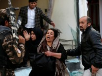 A survivor reacts at the site of a blast in Kabul, Afghanistan