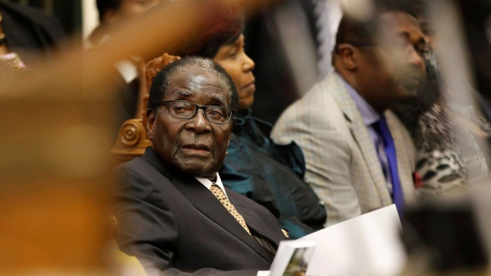 FILE PHOTO -  File photo of Zimbabwe's President Mugabe listening as FM Chinamasa presents the country's 2014 National Budget to Parliament in Harare