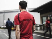 Ein Mitarbeiter mit einem roten Shirt der Firma geht in das Werk von Siemens aufgenommen in Goerlit
