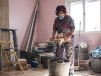 Senior woman using stirrer for mixing paint at construction site model released Symbolfoto property