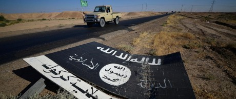 A black sign belonging to Islamic State militants is seen on the road in Al-Al-Fateha military airport south of Hawija