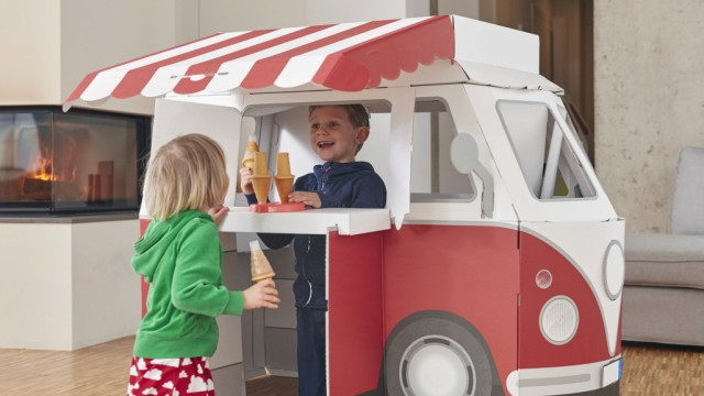 Brother and sister with popsicles and model ice cream van in living room model released Symbolfoto p