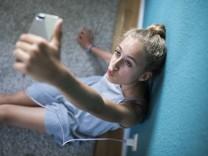 Mädchen sitzt in ihrem Zimmer auf dem Boden und macht selfies MR Mädchen sitzt in ihrem Zimmer und
