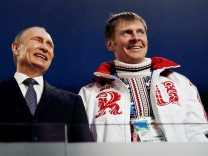 FILE PHOTO: Russian President Putin laughs with Russia's gold medallist bobsleigh athlete Zubkov during the closing ceremony for the 2014 Sochi Winter Olympics