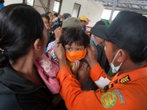 An officer with the disaster management agency BPBD places a mask on child at a shelter for residents sheltering from Mount Agung volcano following its eruption in Bebandem Village, Karangasem, Bali