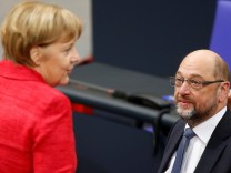 German Chancellor Angela Merkel speaks with Social Democratic Party (SPD) leader Martin Schulz as they attend a meeting of the Bundestag in Berlin
