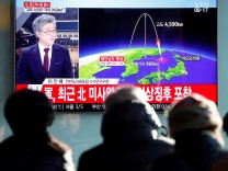 People watch a television broadcast of a news report in Seoul on North Korea firing what appeared to be an ICBM that landed close to Japan