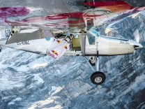 A member of the wingsuit flyers duo, known as the Soul Flyers, is seen in mid-air as he catches up and flies into the open door of Pilatus Porter plane after jumping off the Jungfrau mountain in Lauterbrunnen