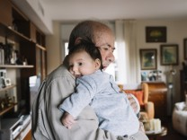 Great grandfather holding baby at home model released Symbolfoto PUBLICATIONxINxGERxSUIxAUTxHUNxONLY