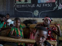 Pupils wait for the French President to enter their classroom during a visit at a school in Ouagadougou