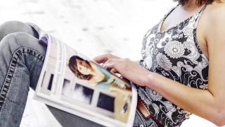 Junge Frau Twen sitzt am Boden an Holzbalken gelehnt liest model released *** Young woman twen