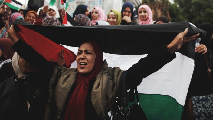 A woman holds a Palestinian flag during a protest against the U.S. intention to move its embassy to Jerusalem and to recognize the city of Jerusalem as the capital of Israel, in Gaza City