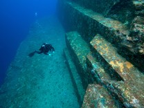 Diver examining the sandstone structure of the Yonaguni undersea monument Yonaguni East China Sea
