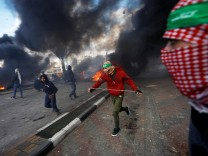 Palestinian protesters run during clashes with Israeli troops at a protest against U.S. President Donald Trump's decision to recognize Jerusalem as the capital of Israel, near the Jewish settlement of Beit El, near the West Bank city of Ramallah