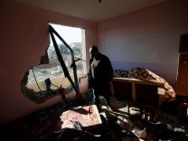 A Palestinian man looks at a nearby militant target in his apartment that was damaged in an Israeli airstrike, in the northern Gaza Strip