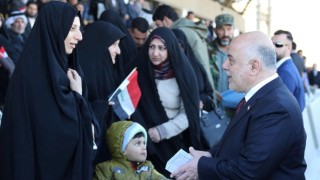 Iraqi Prime Minister Haider al-Abadi greets people during an Iraqi military parade in Baghdad
