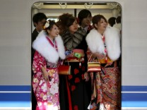 File photo of Japanese women in kimonos riding a train after a ceremony celebrating Coming of Age Day at an amusement park in Tokyo