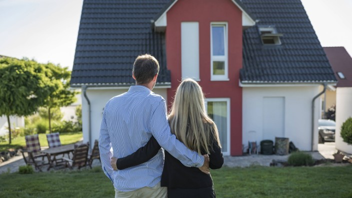Happy couple standing arm in arm in the garden looking at their house model released Symbolfoto prop