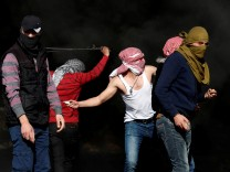 Palestinian protesters throw stones at Israeli forces during a protest against U.S. President Donald Trump's decision to recognize Jerusalem as the capital of Israel, near the Jewish settlement of Beit El, near the West Bank city of Ramallah